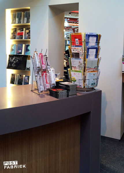 Ansichtkaarten van PLINT in een kaarmolentje op de toonbank bij de kassa