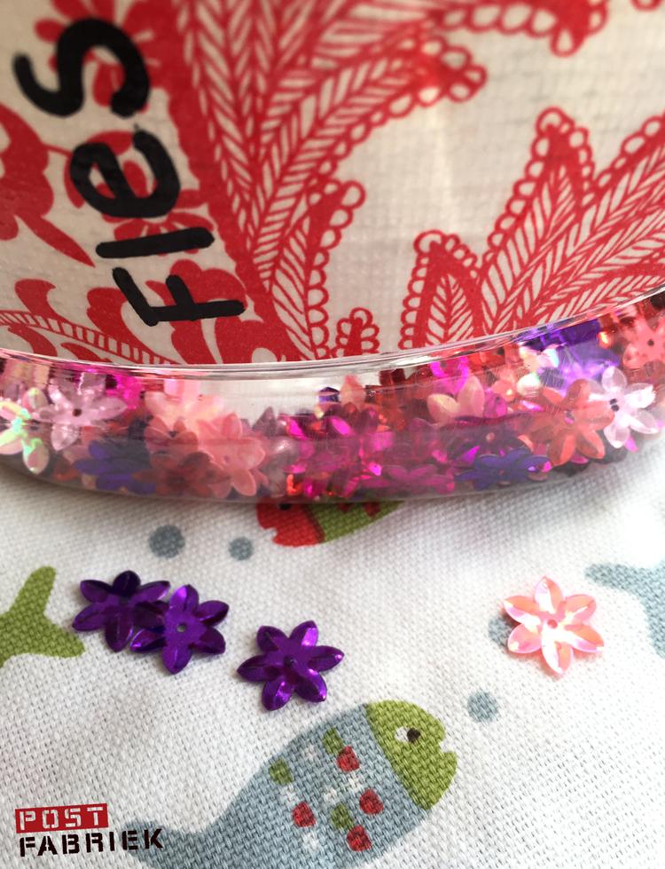Gekleurde bloemetjes op de bodem van de fles