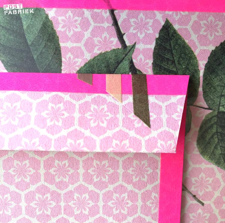 De drie stukjes tape aan de voorkant lopen door naar de achterkant van de envelop