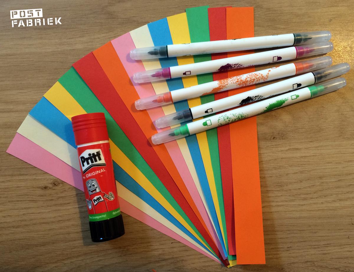 Strookjes gekleurd papier, stiften en lijm
