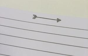 Detail van het pijltje bovenaan de bladzijdes in het notitieboek