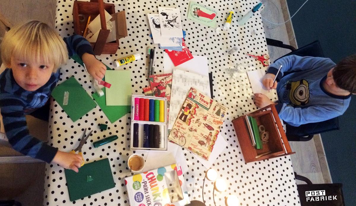 Een rommeltafel vol materialen voor kerstkaarten met kinderen