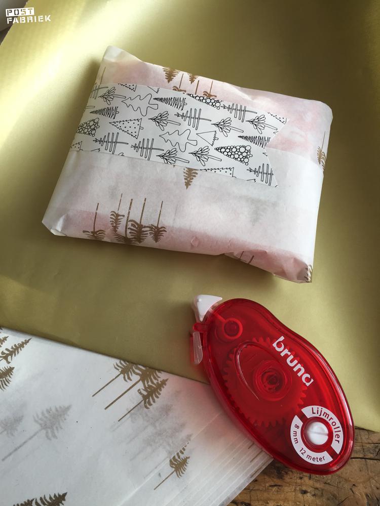 Vloeipapier met gouden boompjes en een langwerpige sticker met boompjes van Vlinders in je buik.