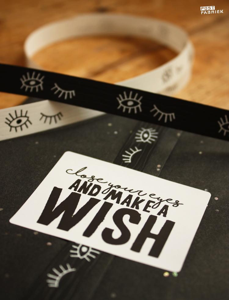Zwart vloeipapier met glitters, lint met oogjes en een sticker met de tekst 'close your eyes and make a wish'. Verkrijgbaar bij Vlinders in je buik.