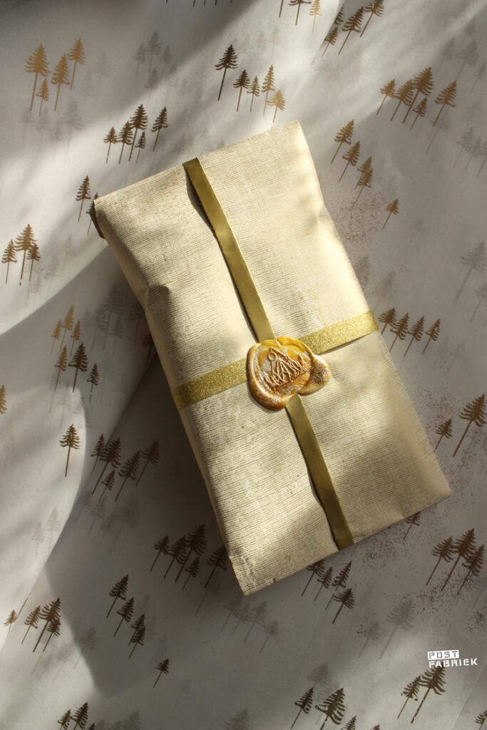 Een pakje in cadeaupapier met een fabric look met een lakzegel. Op de achtergrond zie je vloeipapier met gouden boompjes. Linkjes naar de producten vind je in het blog