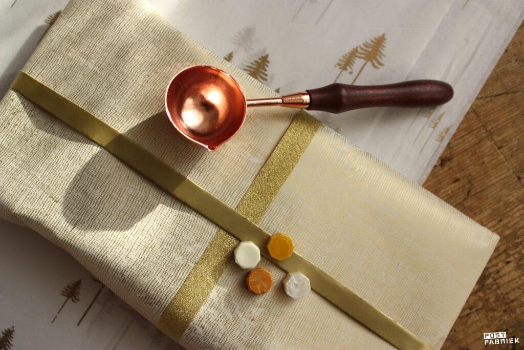 Door een uiteinde van het papier twee keer om te vouwen, kan je beide kanten zien en ontstaat er een band. Voor het pakje hierboven combineerde ik het mooie papiertje met glitterlint en een lakzegel.