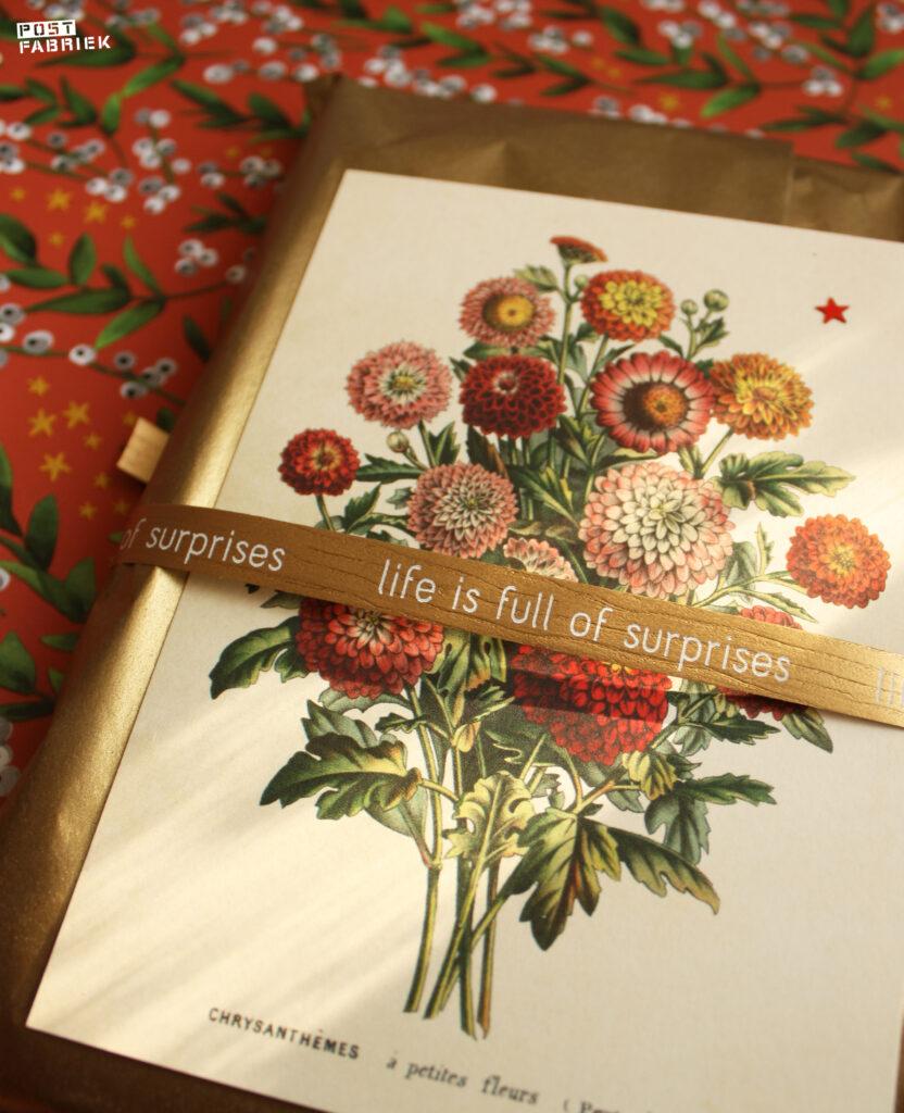 Gouden vloeipapier en lint met de tekst 'Life is full of surprises' van Vlinders in je buik. Het kaartje met bloemen komt van Dille & Kamille.
