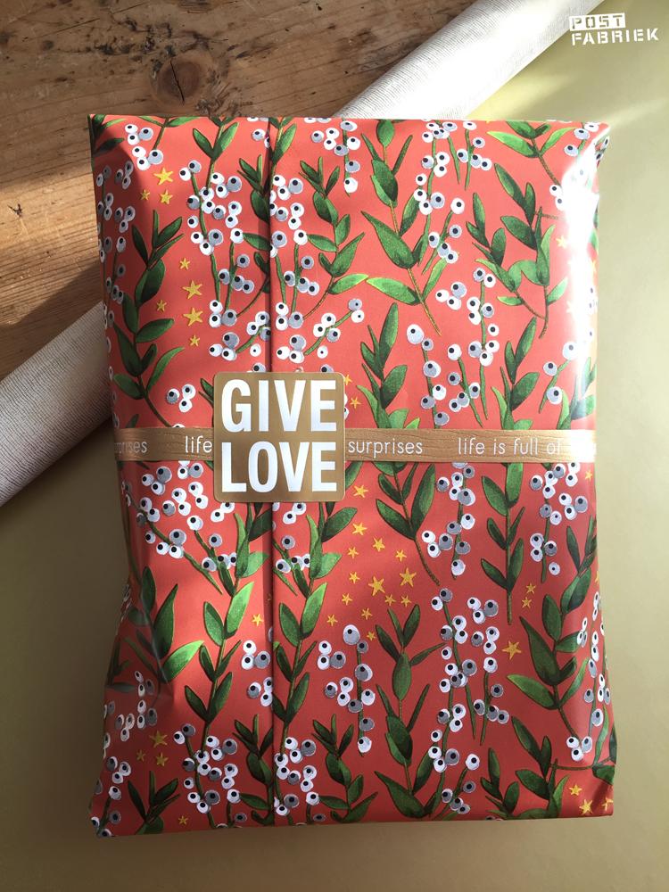 Op het prachtige Winter flower cadeaupapier van Vlinders in je buik zie een winters tafereel van mistletoe en sterretjes op een steenrode achtergrond. Op deze foto zie je hoe ik het papier heb gecombineerd met gouden krullint en een sticker met de tekst 'Give love'.