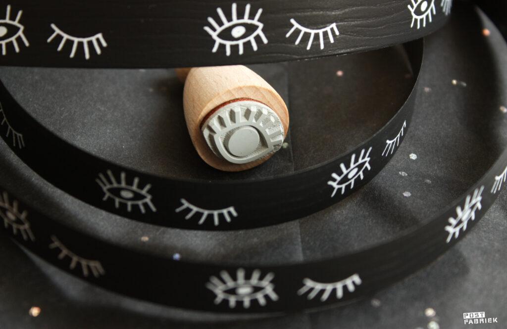 Zwart vloeipapier met glitters en zwart lint met oogjes. De stempel met het oog is van Perlenfischer.