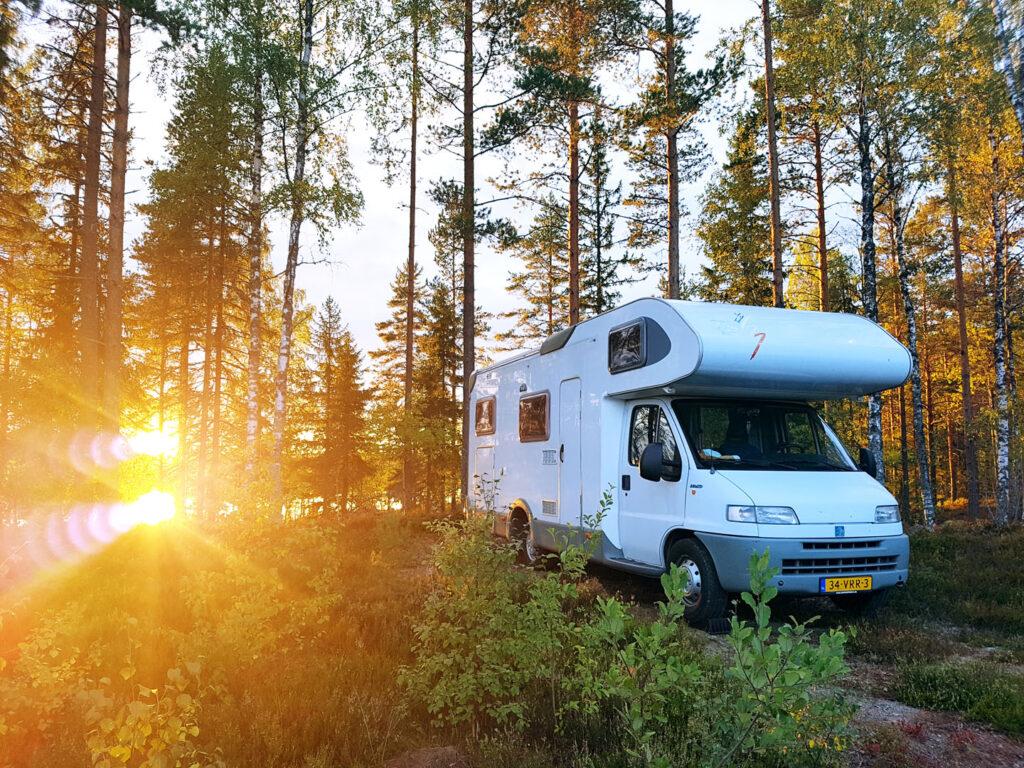 """""""Een jaar lang leefden we in een camper"""". Er staat een witte camper in een bos, links van de camper schijnt tussen de bomen door een laagstaande zon."""