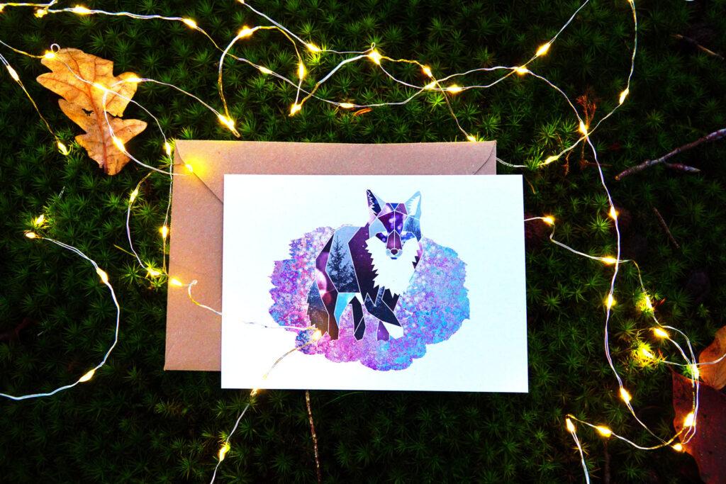 Een door Sarie geïllustreerde geometrische vos met vooral blauwe en paarse kleure en in elk vakje een andere afbeelding, zoals een denneboom en een sterrenhemel. De kaart ligt op een kraftkleurige enveloppe. Daarachter zie je dennentakken en kerstlampjes.
