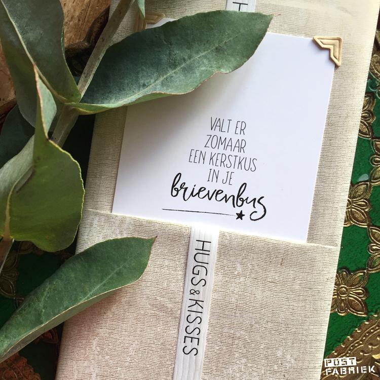 Kaartje met de tekst 'valt er zomaar een kerstkus in je brievenbus', papier met fabric look en lint met de tekst 'Hugs & Kisses. Al deze producten kan je vinden bij Vlinders in je buik.