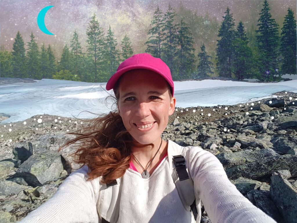 Sarie kijkt lachend in de camera. Achter haar zie je rotsen, sneeuw en dennenbomen met een geïllustreerde maan.