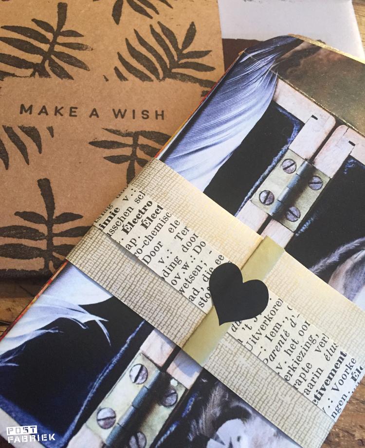 Een pakje zelfgevouwen mini envelopjes samengebonden met een strook papier en een sticker in de vorm van een hart