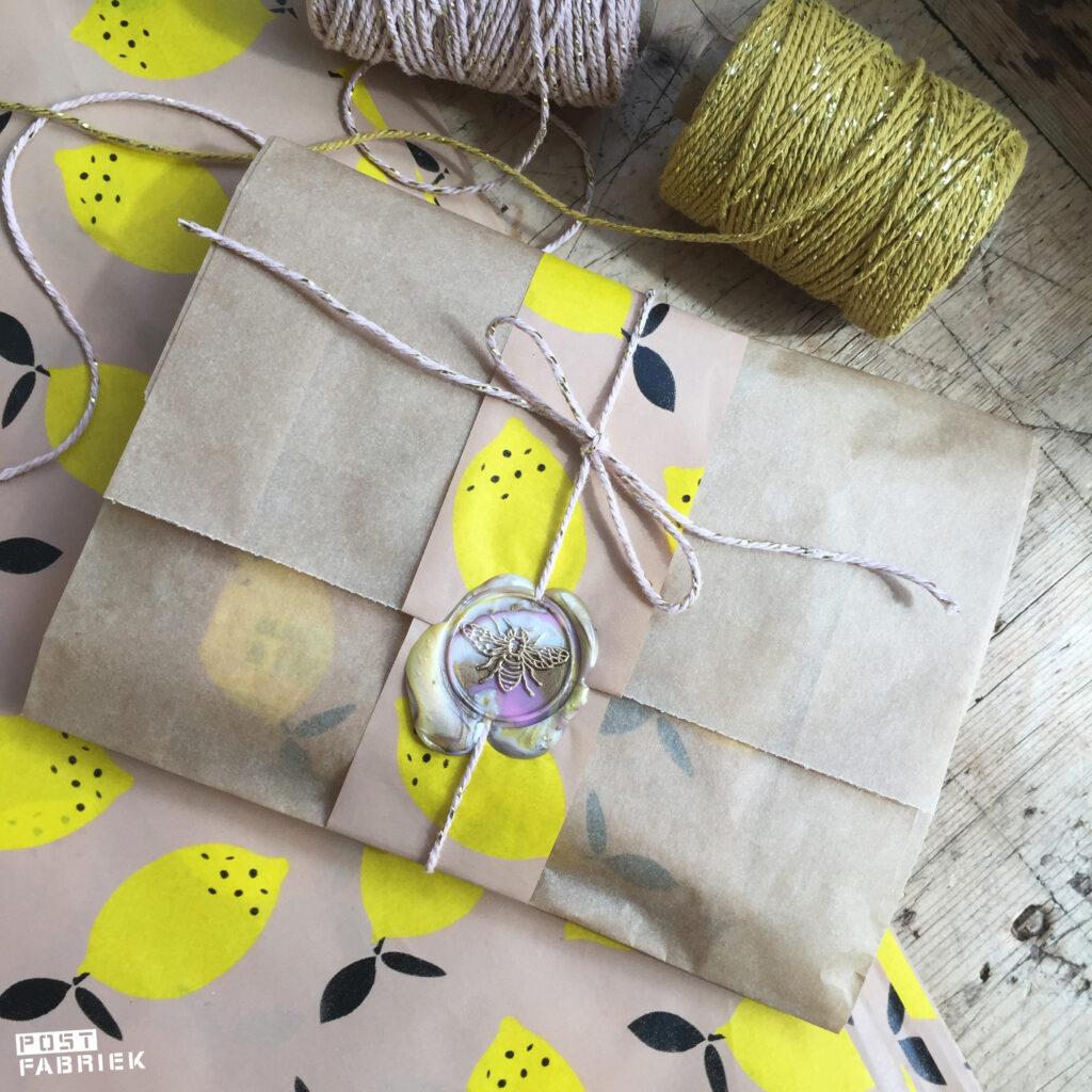 Cadeautje ingepakt met een papieren boterhamzakje van Ecoplaza, vloeipapier van Vlinders in je buik en een lakzegel