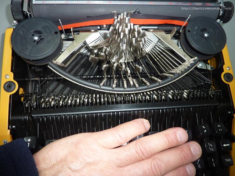 Breng daarna alle typearmen voorzichtig omhoog door met de vlakke hand licht op de toetsen te drukken.
