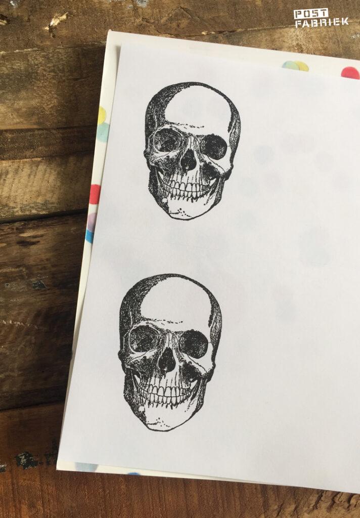 Afdrukken van een stempel van een schedel van het merk '100 proof press' gekocht via de webwinkel van De Posthumuswinkel in Amsterdam