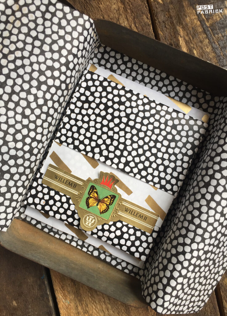 Van het mooie cadeaupapier met de goudkleurige streepjes zijn ook cadeauzakjes. Op deze foto zie je het kleinste zakje met een oud sigarenbandje als sluitzegel.