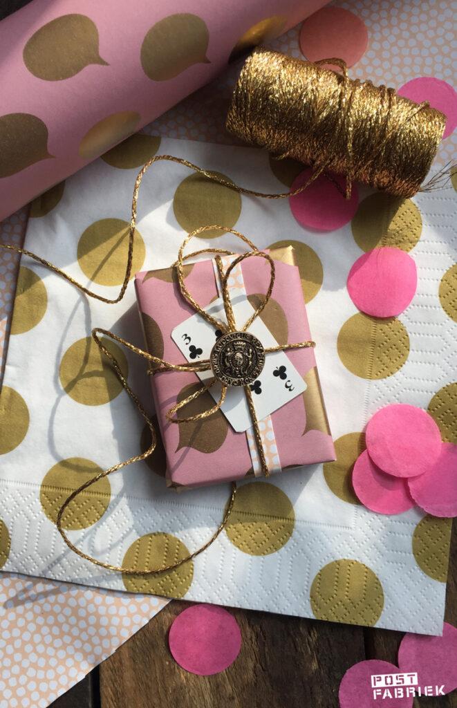 'Let's talk', dubbel bedrukt inpakpapier met goudkleurige tekstwolkjes van Vlinders in je buik. Als je een uiteinde van het papier twee keer omvouwt, ontstaat er een soort band en kan je beide kanten op een pakje zien. Op deze foto zie je hoe ik het cadeaupapier heb gecombineerd met een goudkleurige knoop uit mijn oma's knopendoos en een speelkaart. Het servet komt van HEMA.