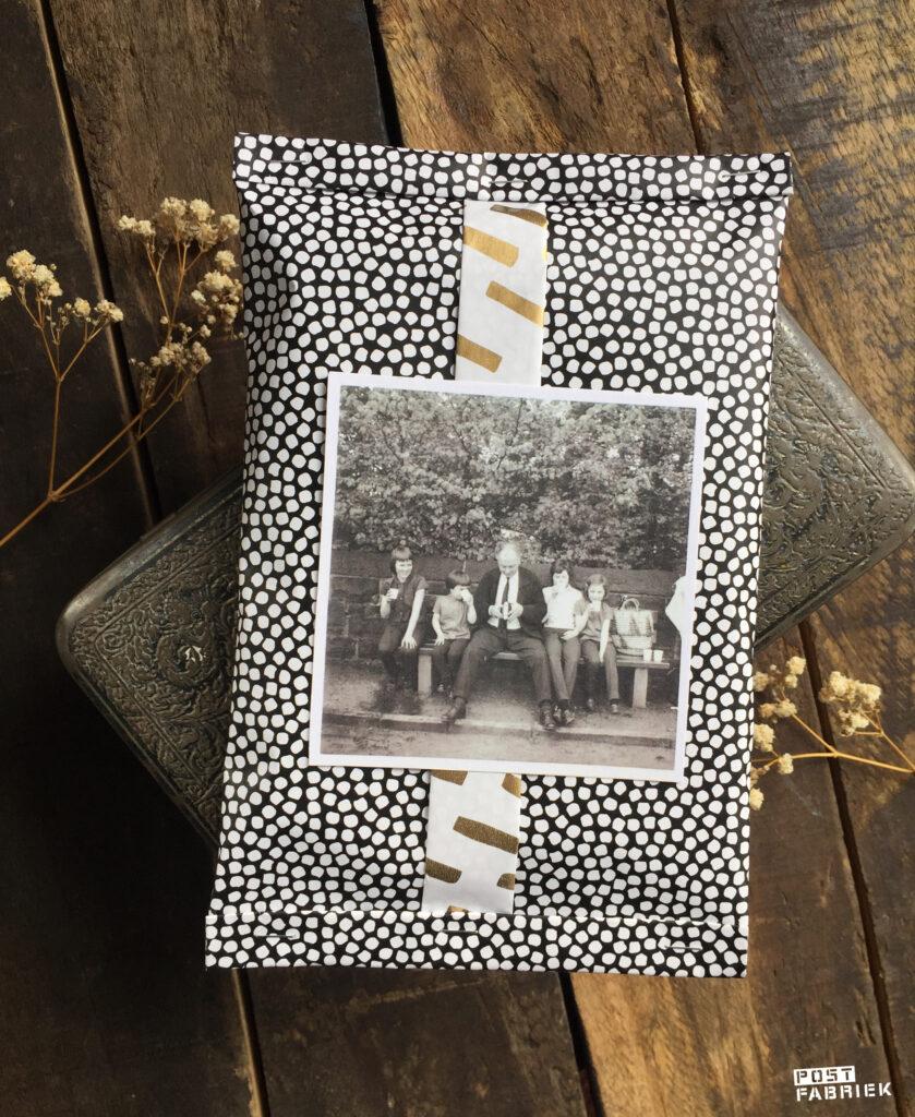 Cadeaupapier 'Open Spaces' van Vlinders in je buik. Als je een uiteinde van het papier twee keer omvouwt, ontstaat er een soort band en kan je beide kanten op een pakje zien. Op deze foto zie je hoe ik het cadeaupapier heb gecombineerd met een kopie van een oude familiefoto.