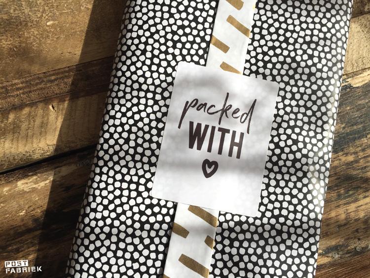 Cadeaupapier 'Open Spaces' van Vlinders in je buik. Als je een uiteinde van het papier twee keer omvouwt, ontstaat er een soort band en kan je beide kanten op een pakje zien. Op deze foto zie je hoe ik het cadeaupapier heb gecombineerd met een zwart/witte sticker met de tekst 'packed with love'.