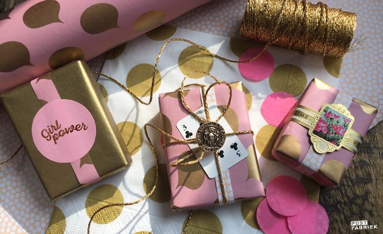 'Let's talk', dubbel bedrukt inpakpapier met goudkleurige tekstwolkjes van Vlinders in je buik. Als je een uiteinde van het papier twee keer omvouwt, ontstaat er een soort band en kan je beide kanten op een pakje zien. Op deze foto zie je hoe ik het cadeaupapier heb gecombineerd met oude en goudkleurige versiersels. Het servet komt van HEMA.