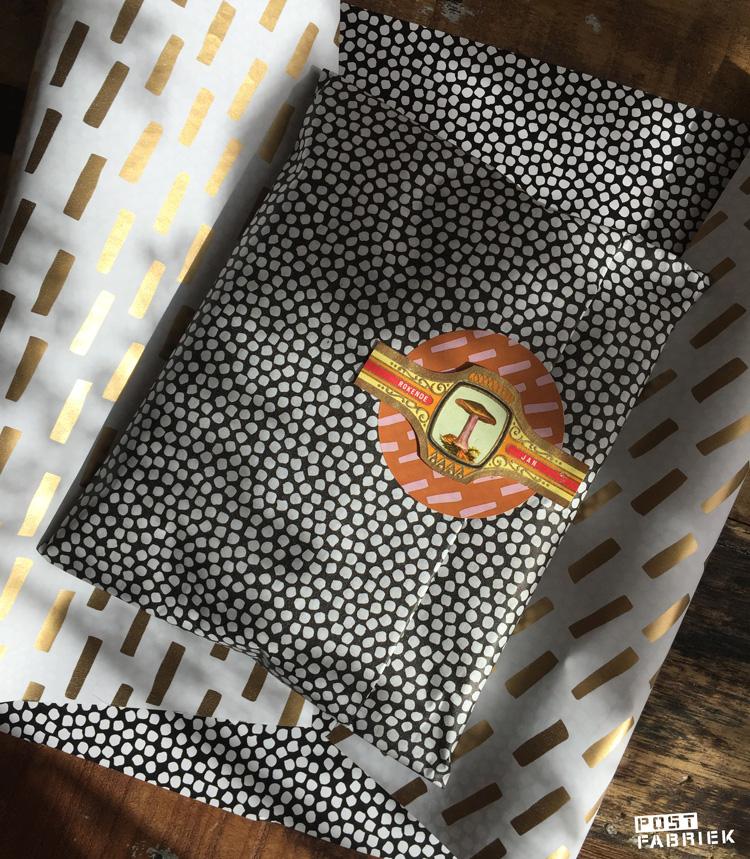 Inpakpapier, vloeipapier en grote ronde sticker van Vlinders in je buik met een oud sigarenbandje.