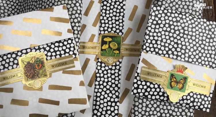 Van het mooie cadeaupapier met de goudkleurige streepjes zijn ook cadeauzakjes. Op deze foto zie je de kleinste zakjes in twee varianten samen met het mooie cadeaupapier. Beide met een oud sigarenbandje als sluitzegel.