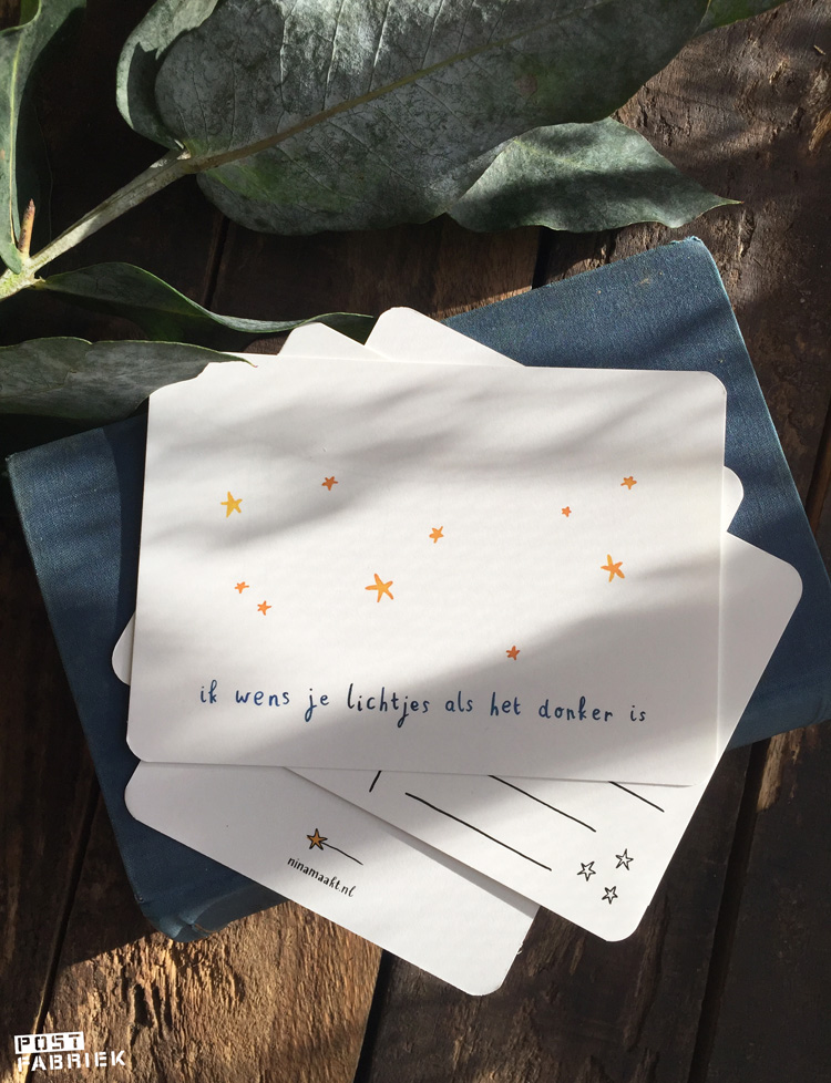 Een kaartje van Ninamaakt met de tekst: 'ik wens je lichtjes als het donker is.' Onder die kaart liggen andere kaarten van Nina. Dat zij haar kaarten met heel veel liefde maakt, is aan de voor- én achterkant te zien.