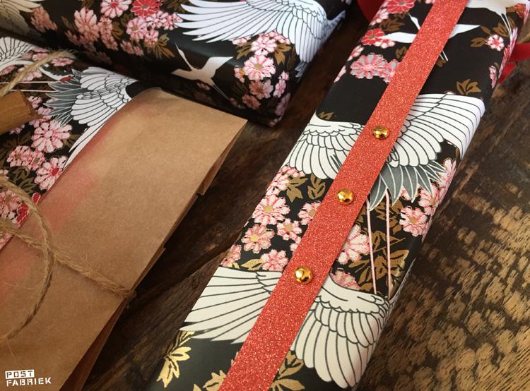 Het prachtige Kimono papier met koraalrood lint en goudkleurige splitpennen.