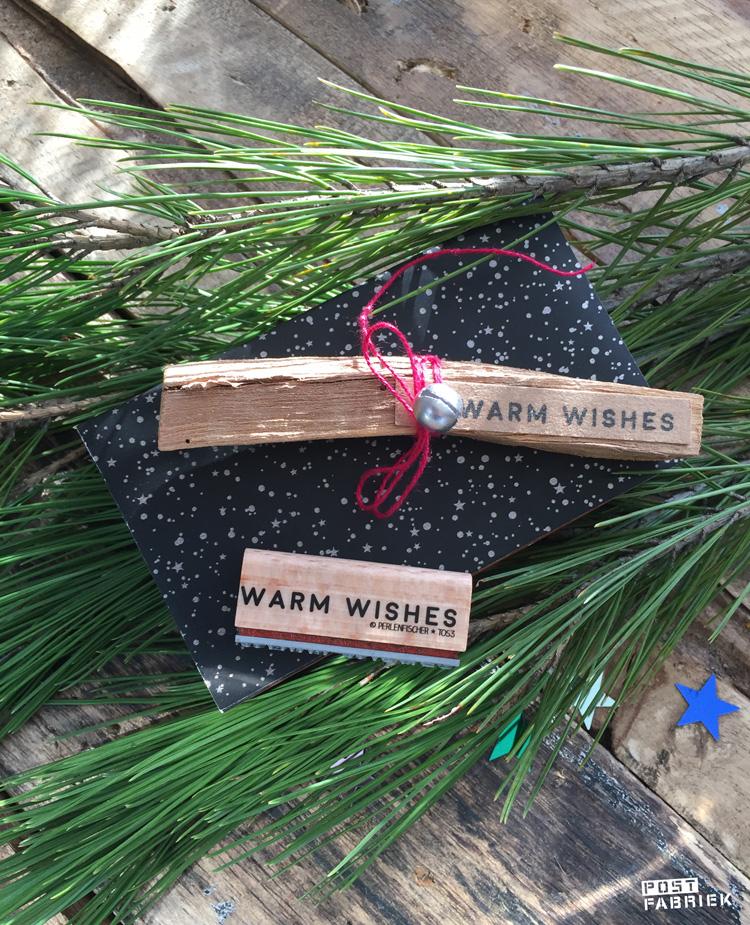 Op deze foto zie je een stempel van het merk 'Perlenfischer' met de tekst 'warm wishes'. Op het label zie je een afdruk van de stempel.