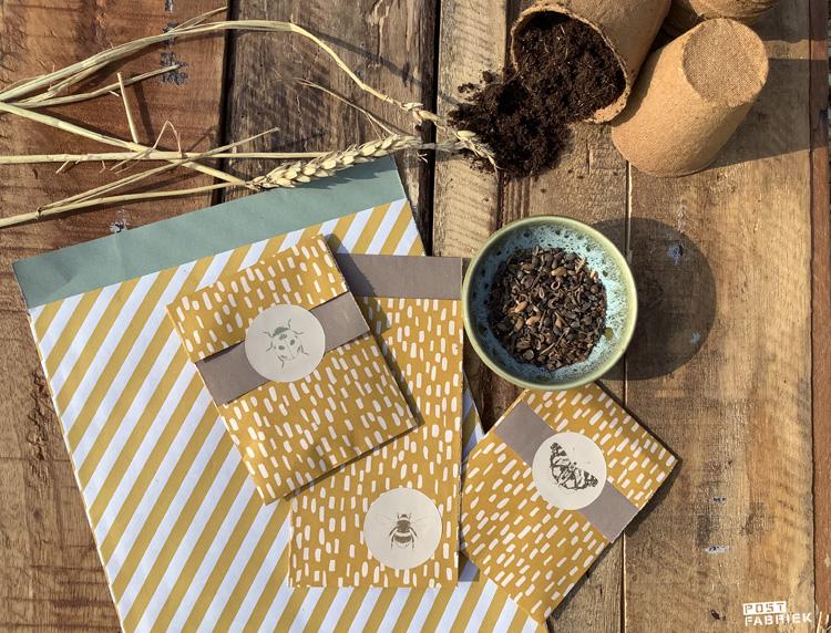 Kleine cadeauzakjes met insecten stickers als sluitzegel. Op de beige stickers staan hommels, vlinders en lieveheersbeestjes met goudfolie gedrukt.
