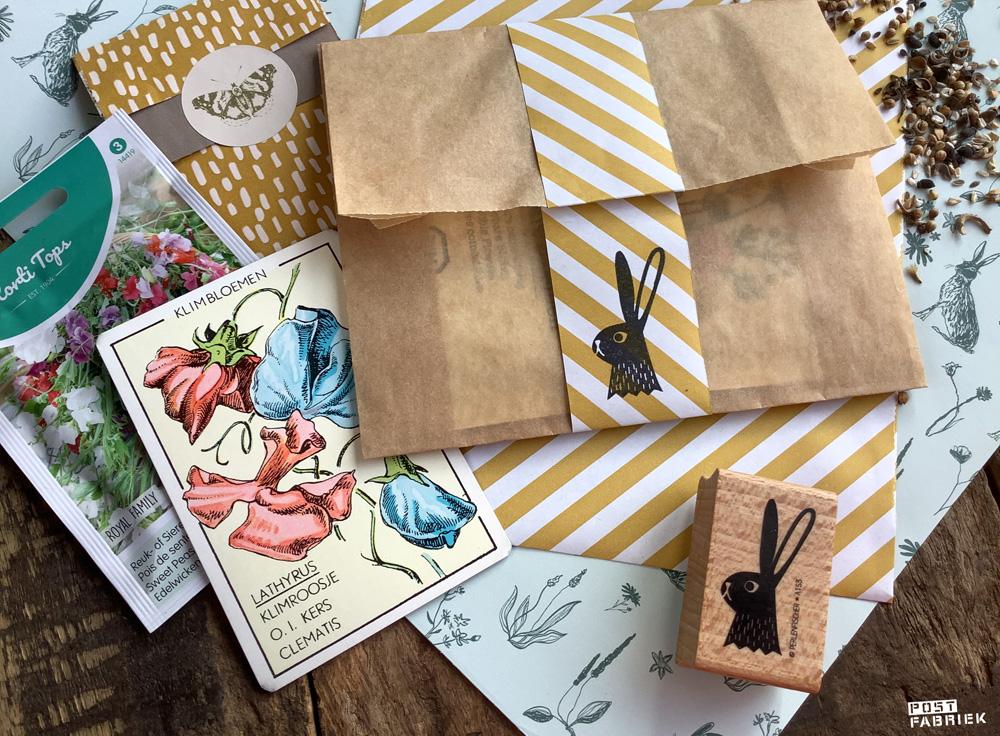 Op deze foto zie je lichtblauw papier met hazen en bloemen. Daar bovenop liggen zakjes, bloemzaden, een kaart uit een oud kwartet spel en een stempel van Perlenfischer.