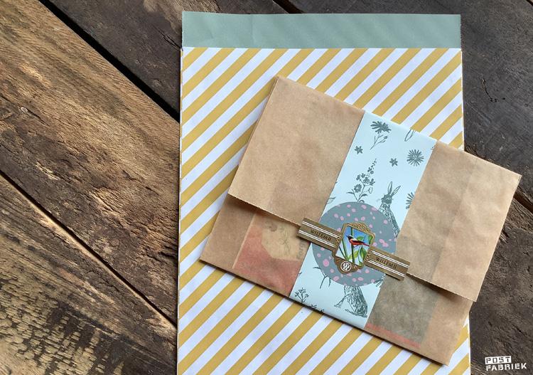 Een geel/wit gestreept zakje van House of products en een papieren boterhamzakje van Ekoplaza gecombineerd met een strook van het blauwe papier met hazen en bloemen. Hier heb ik een sticker en sigarenbandje als sluitsticker gebruikt.