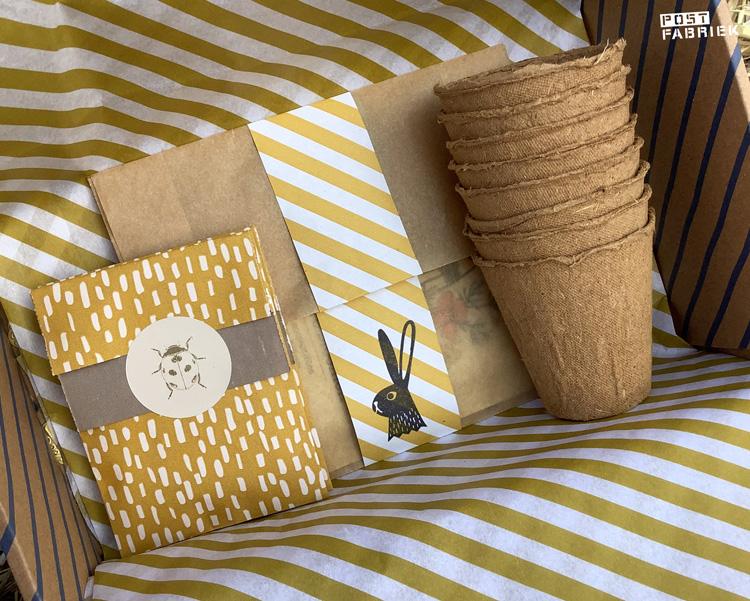 Een pakketdoosje met daarin geel/wit gestreept vloeipapier van House of Products, verschillende cadeauzakjes en biologisch afbreekbare potjes.