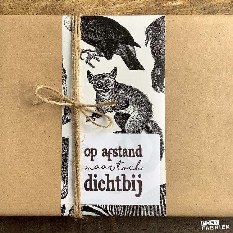 Kraftpapier met een strook van het cadeaupapier met dieren, jute touw en een sticker van LotsofLo met de tekst 'op afstand maar toch dichtbij'.