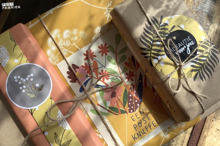 Verschillende pakjes ingepakt met papieren moois van Vlinders in je buik en een kaartje van Zintenz met de tekst 'een postknuffel'.