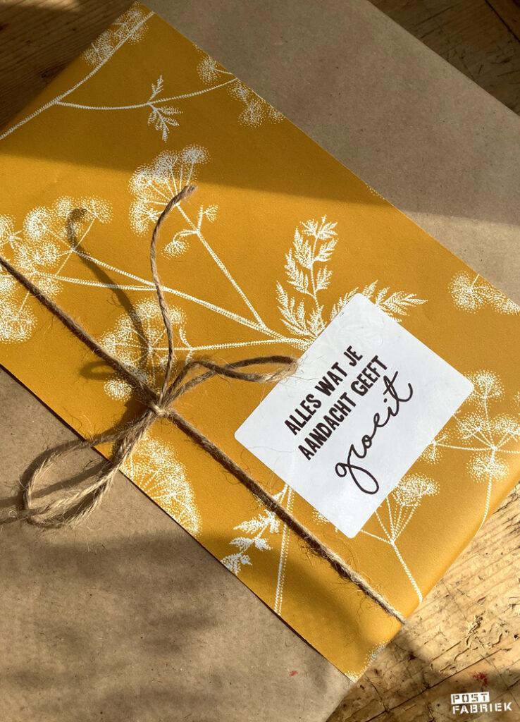 Een cadeautje ingepakt in kraftpapier dat ik heb versierd met cadeaupapier en sticker van Vlinders in je buik. Het fluitenkruid dessin is een ontwerp van Fine Forest voor Ompak. De sticker is een ontwerp van LotsofLo.