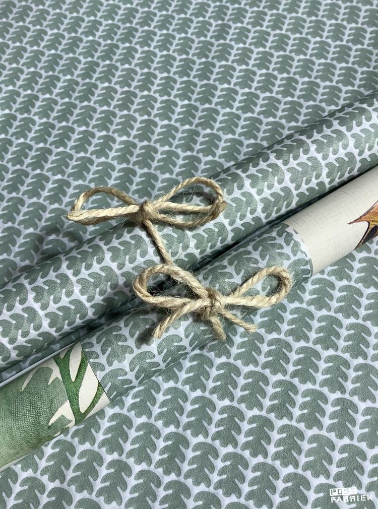 Het onderwaterpapiertje opgerold met een band van het mooie vloeipapier met eikenblaadjes.
