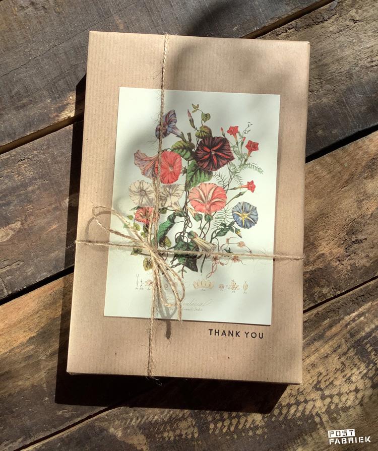 Een cadeautje ingepakt in kraftpapier met een stempel van Perlenfischer, jute touw en een kaartje van Sköna Ting via Dille & Kamille.