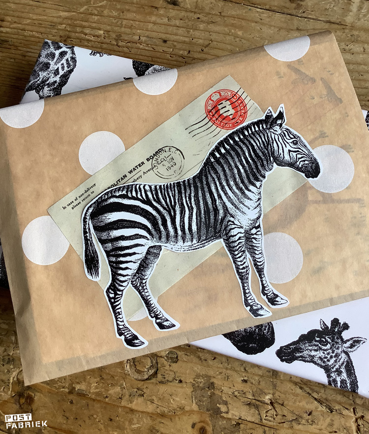 Een papieren boterhamzakje van HEMA dat ik met een plaatje uit Filatelie en een zebra uit het cadeaupapier heb versierd.