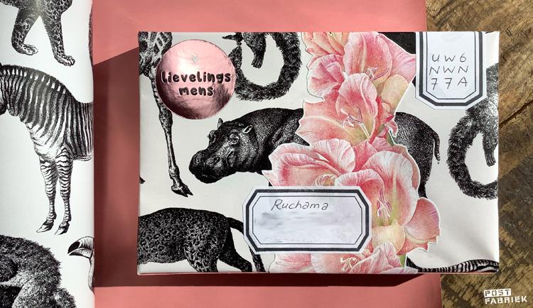 Cadeaupapier 'Let's go to the Zoo' van Vlinders in je buik om een lege verpakking maakt een luxe uitziend brievenbusdoosje. In de linkerbovenhoek zie je een sticker met de tekst 'Lievelingsmens', ook van Vlinders in je buik. De roze bloemen knipte ik uit een boek over bloemen en planten dat ik in de kringloop vond. De stickers waar ik het adres en de postzegelcode op schreef, maakte ik zelf met behulp ban een stempel van het merk 'Perlenfischer'.