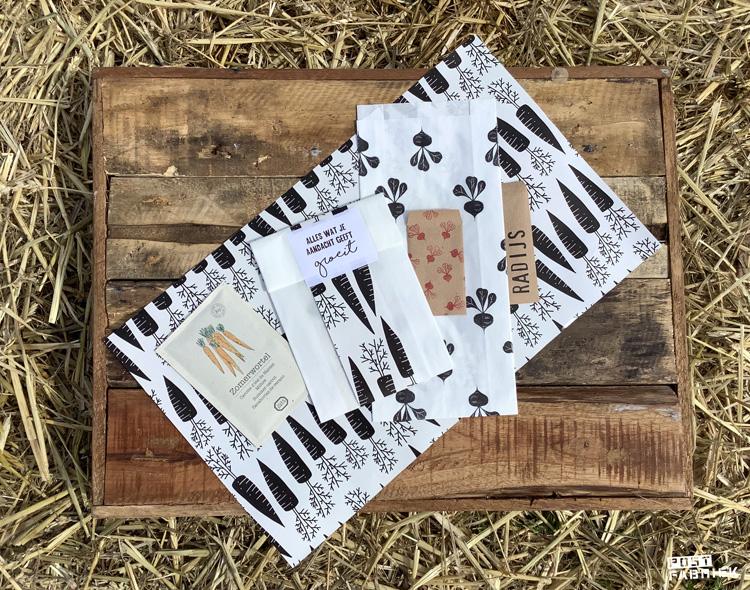 Op het dienblad ligt een stuk van het zwart-witte cadeaupapier met wortelen dat ik bij Vlinders in je buik bestelde. Daarop zie je verschil zakjes: een zakje met zaadjes, een versierd papieren boterhamzakje en bestempelde zakjes.